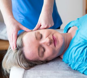 Patricia at Sligo Kinesiology relaxing the jaw muscles to help neck and jaw pain